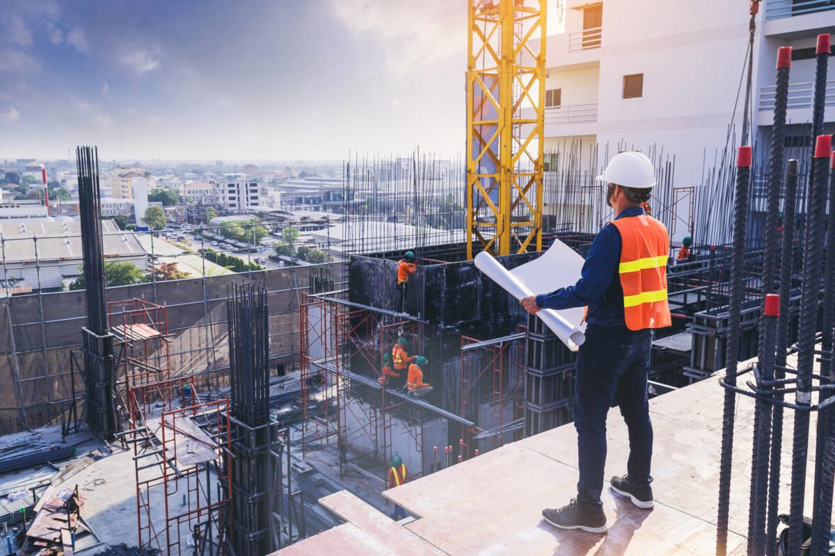 engenheiro civil segurando planta e olhando para obra